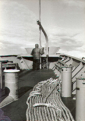 An able seaman stands iceberg lookout on the bow of the freighter USNS Southern Cross during a re-supply mission to McMurdo Station, Antarctica; circa 1981.