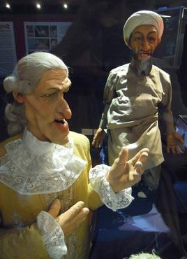 Puppets of a Court Flunkey and Osama bin Laden. The face of the Flunkey is a caricature of 18th-century cartoonist James Gillray, the father of British political cartooning. Flunkey and Osama.jpg