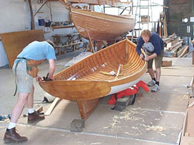 Arques students working on a Black Cat 15 foot lapstrake daysailor