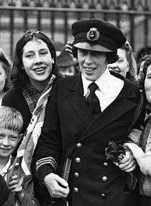 Black and white photograph of Victoria Drummond on receiving her MBE. She is wearing a naval uniform and surrounded by women and children.