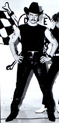 A 23-year old man stands akimbo, facing forward. He wears a black cowboy hat, sleeveless t-shirt, leather pants, a band on his left wrist and pointed shoes. He has a moustache and has tattoos on his upper arms. He is in front of a sign/art work which is mostly obscured but with a chequered flag, bones and the letters D and E visible. To his left and behind him is another man partly cut off at the edge of the image.