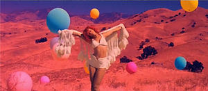 Rihanna standing in the middle of a field, with a shawl, surrounded by floating balloons