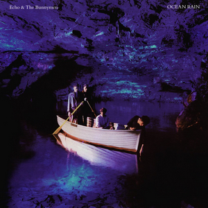 An album cover showing four men in a rowing boat inside a blue lit sea cave. Two men are stood side-by-side at the back of the boat each holding an oar, the third man is sat in the centre of the boat and the fourth is leaning over the front of the boat with his hand in the water. The band's name is in the top-left of the cover and the album's name is in the top-right, both in white text.