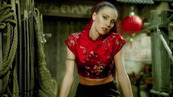 A scene from the music video, featuring Chisholm dressed in a red cheongsam, in a segment based on the film Year of the Dragon Spice Girls - Too Much (music video).png
