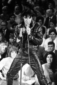 Presley, wearing a tight black leather jacket with upturned collar, black leather wristbands, and black leather pants, holds a microphone with a long cord. His hair, which looks black as well, falls across his forehead. In front of him is an empty microphone stand. Behind, beginning below stage level and rising up, audience members watch him. A young woman with long black hair in the front row gazes up ecstatically.