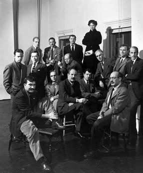 Several rows of men in suits. The first row is sitting, and two rows of men stand behind them. A woman, standing noticeably above the men, is behind the last row of standing men.