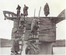 Three soldiers are standing on top of a partially destroyed bridge, while other soldiers climb up two roughly constructed ladders with their rifles slung over their shoulders while carrying stores.