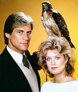 A man in a suit, holding a hawk. Beside him a blonde woman.