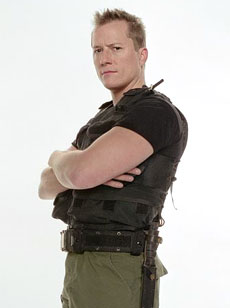 Upper body shot of a stern-looking young man with spiked blond hair, clean shaven, in a black t-shirt and wearing a military belt.
