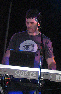 Upper body shot of a 34-year-old man. He is partly obscured by a keyboard and microphone in front of him. He has short dark hair and wears a dark tee-shirt, which has a large open eye logo. His eyes are directed down and slightly to his right. His arms are raised to the keyboard, but his hands are obscured. The lettering O-A-S-Y-S is visible on the back of the synthesiser with an additional K at the right.