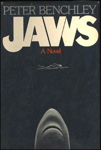 "A black cover depicting a woman swimming and a shark coming towards her from below. Atop the cover is written ""Peter Benchley"", ""Jaws"" and ""A Novel""."