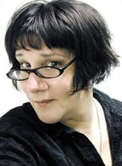 A middle-aged Caucasian woman with medium-to-short black hair and glasses peers at the camera.