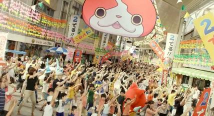 A screenshot from the commercial for Yo-kai Watch 2, depicting a crowd of people performing Yo-kai Exercise No. 1. An image of Jibanyan's face appears overhead. Yo-Kai Watch 2 TVC Screenshot.jpg