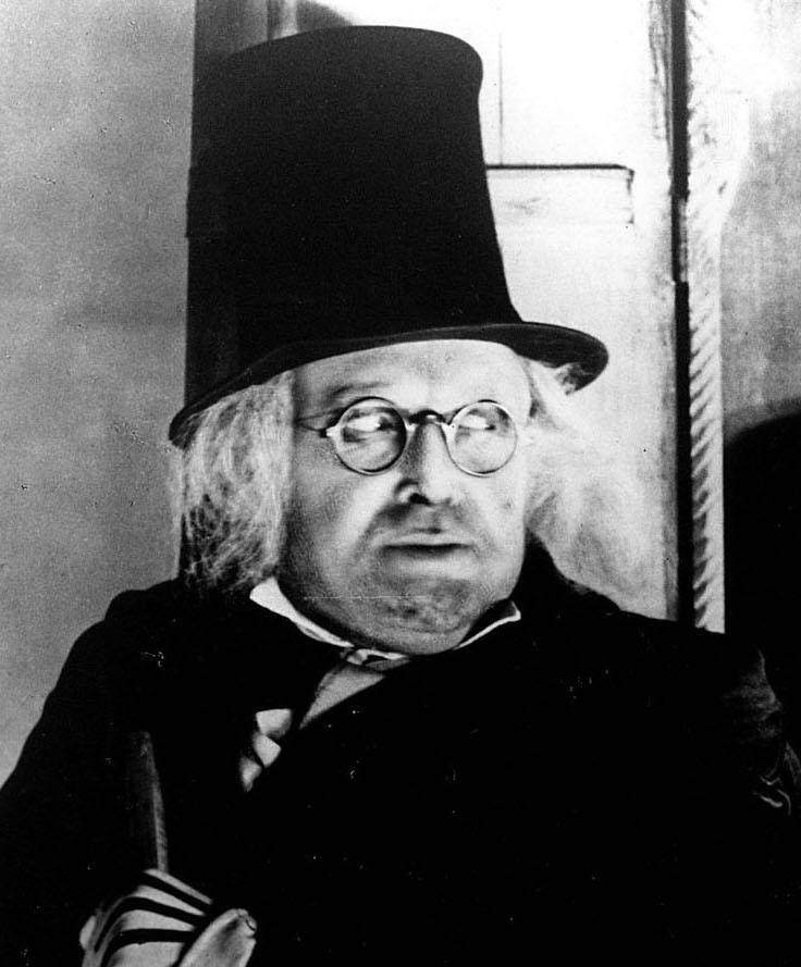 A close-up of a man with a black coat, round-framed glasses, a tall black top hat, and dissheveled white hair. The man is looking toward the right out of the picture.