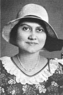 A smiling woman with olive skin and dark hair, wearing a hat with a wide brim, and a floral print dress or blouse with a ruffled white collar.