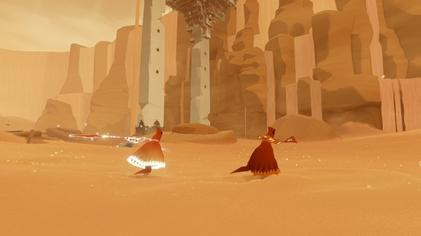 A red-robed figure runs through the sand in front of some stone ruins, accompanies by another figure. The trailing figure's robe and scarf are glowing.