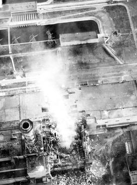 Radioactive steam plumes continued to be generated days after the initial explosion, as evidenced here on 3 May 1986 due to decay heat. The roof of the turbine hall is damaged (image centre). Roof of the adjacent reactor 3 (image lower left) shows minor fire damage. Igor Kostin took some of the clearer pictures of the roof of the buildings when he was physically present on the roof of reactor 3, in June of that year.[48]