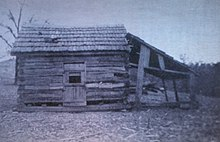A log cabin with some logs missing and a lean-to attached to its side