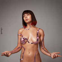 A nude Charli XCX covered by ropes in front of a gray background
