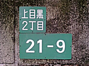 Japanese addressing system - A sign displaying the town address Kamimeguro 2 chōme; block (gaiku) 21, building (bangō) 9 identifies the residential address. The upper plaque is the district name plate (町名板, chōmei ban) and the lower, the residential number plate (住居番号板, jūkyo bangō ban).