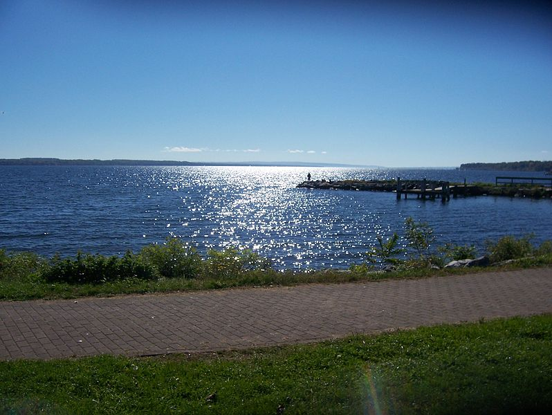 A walkway beside the water, a pier in the distance with someone standing at the tip, and the reflection of sunlight on the lake.