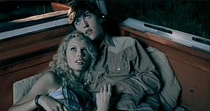 """Tim McGraw (song) - Swift and Clayton Collins lying atop the back of a 1970 Chevrolet C-10 Cheyenne in the music video for """"Tim McGraw""""."""