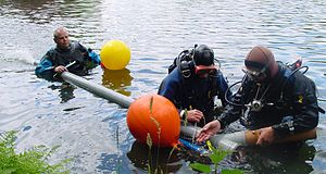 Water eductor - Archaeologists preparing a water dredge on a shallow site