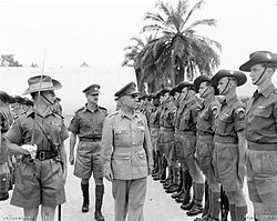 A senior military officer walking among a line of soldiers.