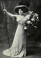 Женщина стоит в драматической позе, правая рука поднята, левая держит большой букет.  На ней длинное вечернее платье и широкополая шляпа.