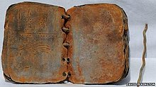 A weathered looking ring-bound book laid open.