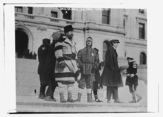 Louis W. Hill - Hill (wearing a broad striped blanket coat) in a group watching the 1916 Saint Paul Winter Carnival parade from the steps of the Minnesota State Capitol in St. Paul, Minnesota