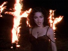 A brunette woman in front of a pair of burning crosses. The woman is wearing a dark, brown dress and looks towards the camera