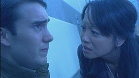 A man in a soldier's uniform looking anguished, and a British woman of Asian descent looking at him, concerned