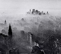 A black-and-white, panoramic view of New York City as seen from a great height. A vast number of buildings and skyscrapers can be seen. A hazy, smoky gas overlays the entire city like a blanket, with a fairly clear skyline only in the far distance at the horizon. Near the closest buildings, the smog appears thin and wispy. The smog appears thicker and thicker around buildings that are farther away from the photographer's position, until shorter buildings near the horizon are almost entirely shrouded and impossible to see under a thick layer of smog. Near the horizon, the clustered tops of tall skyscrapers emerge from within the smog.