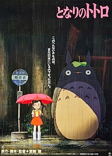 An early version of Satsuki is near a bus stop on a rainy day holding her umbrella. Standing next to her is Totoro. Text above them reveals the film's title and below them is the film's credits.