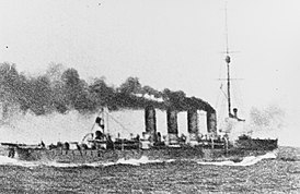 Waves crash against the bow of a cruiser as it steams ahead with large clouds of smoke coming out of all four of its funnels.