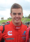 A teenaged man wearing red racing overalls with sponsors logos is smiling at the camera