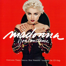 Madonna with short, blond hair, wearing a black dress, with her hands folded against her breasts and standing in front of a red background. She has a Spanish hat attached to her neck.