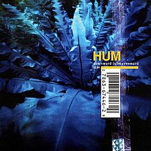 "A photograph of leaves tinted blue with the word ""HUM"" written in gold and ""DOWNWARD IS HEAVENWARD"" below that in white. The cover has a large UPC code across it and a simulation of a sticker attached to it."