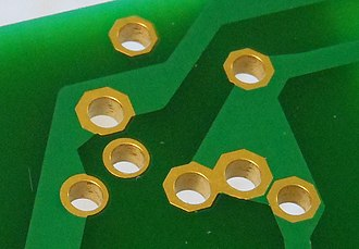 Through-hole technology - Close-up view of an electronic circuit board showing component lead holes (gold-plated) with through-hole plating up the sides of the hole to connect tracks on both sides of the board. The holes are circa 1mm diameter.