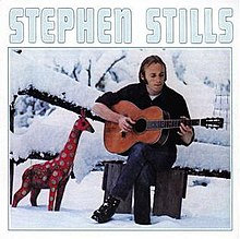 Stephen Stills sitting outside in the snow and playing a guitar, with a toy giraffe nearby