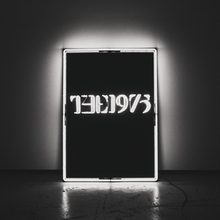 A black-and-white photo showcasing a rectangular glowing neon sign against a wall in the near-center saying The 1975