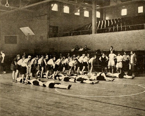 Wills Gymnasium - Interior view in 1930 during a physical education class. Balcony seats, windows, and lower-level bleacher seating can be seen in the background.