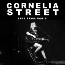 "A black-and-white photograph of Swift playing the guitar. The white text ""Cornelia Street Live from Paris"" is written above her."