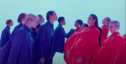Dua Lipa und ihre Besatzung von Frauen in blauen Anzügen beugen sich in einem blau getönten Raum zu ihren Klonen, die rot tragen.