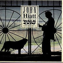 A black outline of Hiatt holding a guitar and a dog looking at one another