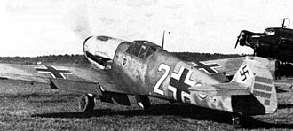 "A black and white photograph a propeller driven fighter aircraft viewed from the rear-left. The aircraft is on a grass field, engine appears to be running. It bears three black and white crosses, two on the upper wings and one on the left side of the fuselage besides a large number ""2"". The tail rudder shows a black swastika plus rudder bears approximately 33 small vertical black lines arranged in three groups of varying length."