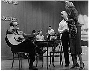 Red Foley sitting onstage at a table, left, with guitar on his lap; director Bryan Bisney and actress Fran Allison stand to the right