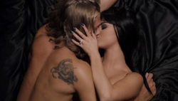 Selena Gomez and Christopher Mason sharing a kiss, half-naked on a black bed.