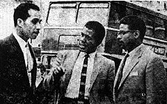 Three Afro-Caribbean men in conversation; behind them can be seen the upper part of a double-decker bus.
